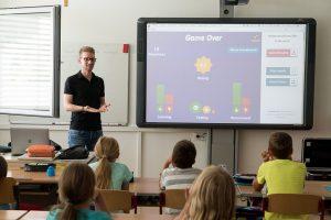 Lehrer vor Schülern am Interaktiven Board