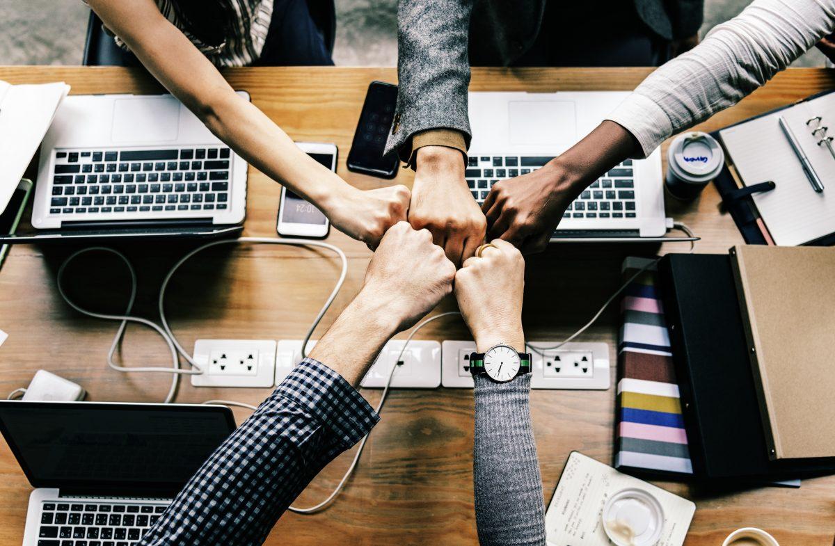 5 Fäuste unterschiedlicher Personen bilden einenStern über einem mit Laptops gefüllten Schreibtisch